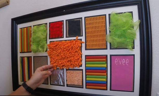 Un mur sensoriel Montessori avec différents tissus (texture et couleurs)